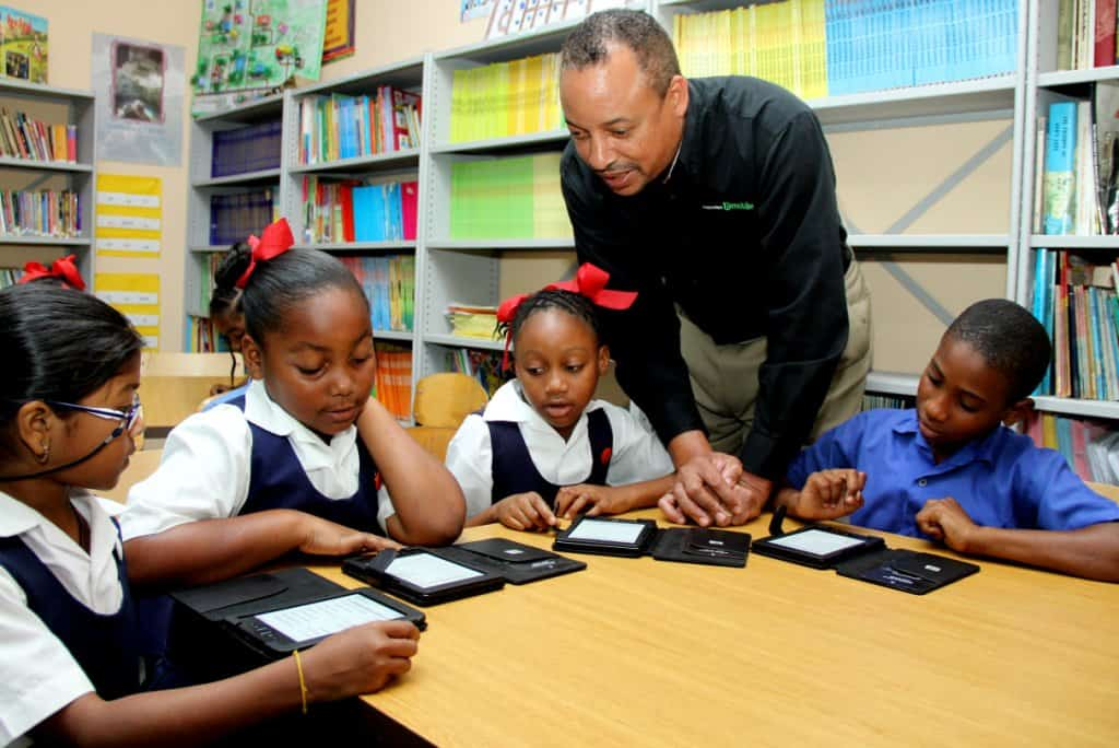 Couva Anglican Primary School students discuss the books on their new tablets with George Hill, Acting CEO, blink   bmobile.