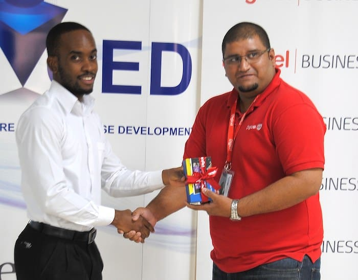 Digicel Be Extraordinary winner Gyasi Ambrose (left) being presented with his prize by Digicel's Product Manager, Dinesh Ramsundar.